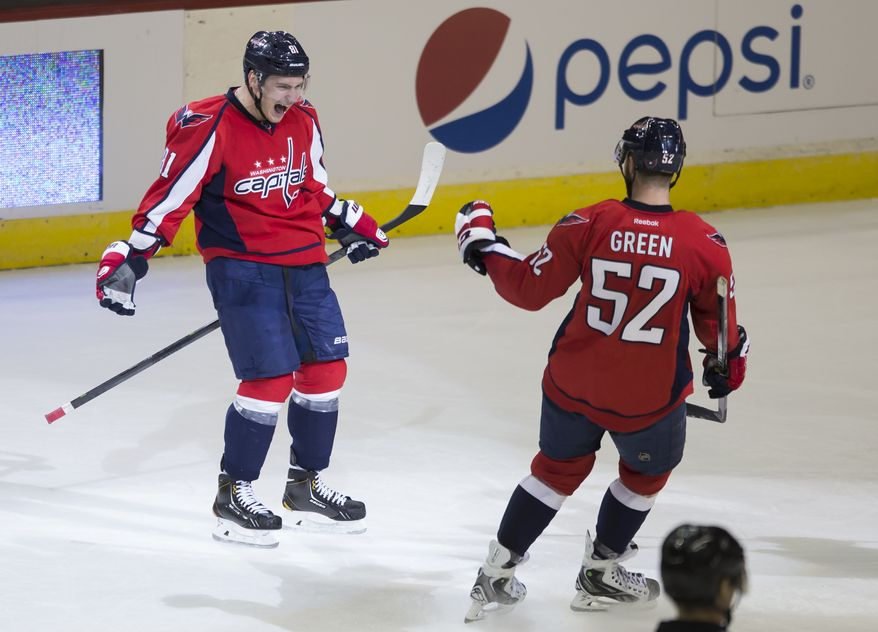 Washington Capitals defenseman Dmitry Orlov, left, celebrates his goal with defenseman Mike Green during the second period of an NHL hockey game against the Philadelphia Flyers, Sunday, March 2, 2014, in Washington. (AP Photo/ Evan Vucci)