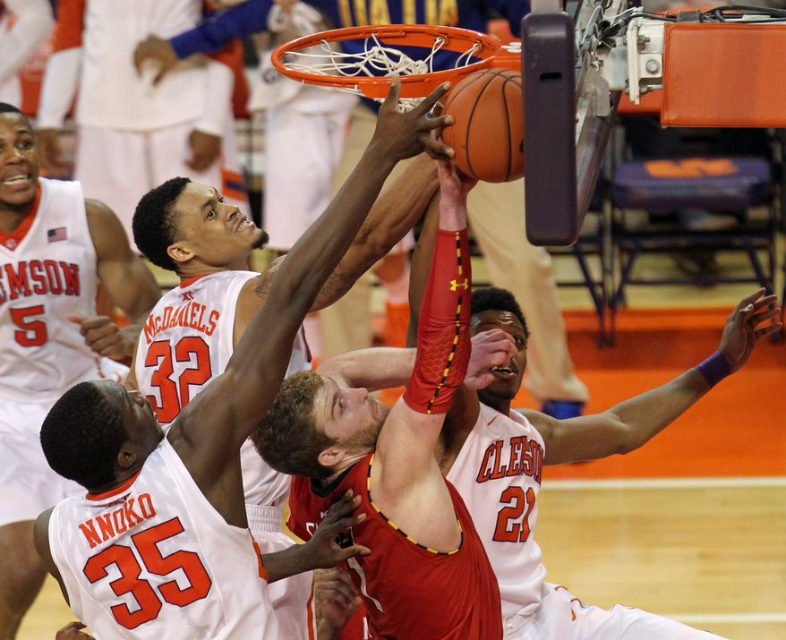 Clemson's Landry Nnoko (35), K.J. McDaniels (32), Demarcus Harrison (21) and Maryland's Evan Smotrycz trap the ball against the glass as they battle for a rebound in the first overtime of their NCAA college basketball game, Sunday, March 2, 2014 in Clemson. S.C. Clemson won, 77-73 in double overtime. (AP Photo/Anderson Independent-Mail, Mark Crammer) GREENVILLE NEWS - OUT; SENECA JOURNAL - OUT