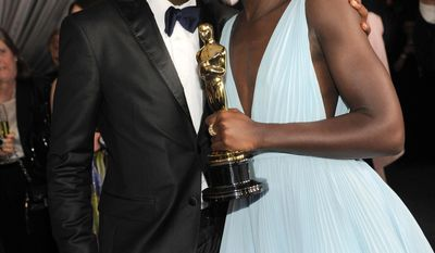 "Lupita Nyong'o, winner of the award for best actress in a supporting role for ""12 Years a Slave"", right, and her brother Peter attend the Governors Ball after the Oscars on Sunday, March 2, 2014, at the Dolby Theatre in Los Angeles.  (Photo by Chris Pizzello/Invision/AP)"
