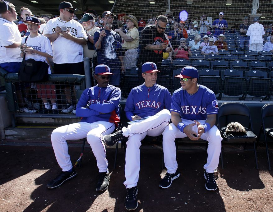 Texas Rangers' Ron Washington and bench coach Tim Bogar, center, talk with Seattle Seahawks quarterback Russell Wilson, right, before the start of a spring training exhibition baseball game against the Cleveland Indians, Monday, March 3, 2014, in Surprise , Ariz. (AP Photo/Tony Gutierrez)