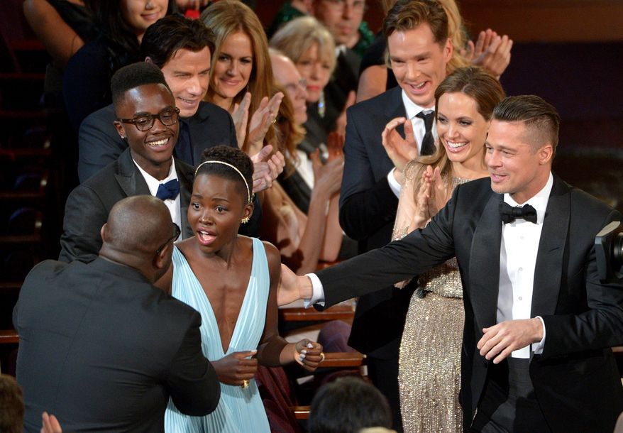 """Director Steve McQueen, left, congratulates Lupita Nyong'o on her win for best actress in a supporting role for """"12 Years a Slave"""" as,  from background left, her brother Peter, John Travolta, Kelly Preston, Benedict Cumberbatch, Angelina Jolie, and Brad Pitt look on during the Oscars at the Dolby Theatre on Sunday, March 2, 2014, in Los Angeles.  (Photo by John Shearer/Invision/AP)"""