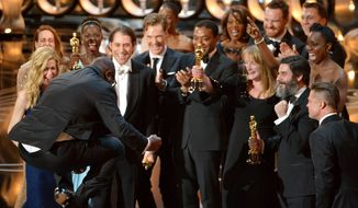 """Director Steve McQueen, left, celebrates with the cast and crew of """"12 Years a Slave"""" as they accept the award for best picture during the Oscars at the Dolby Theatre on Sunday, March 2, 2014, in Los Angeles.  (Photo by John Shearer/Invision/AP)"""
