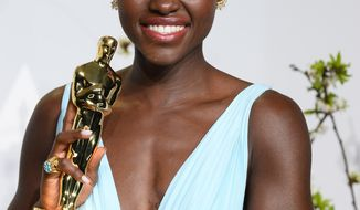 "Lupita Nyong'o poses in the press room with the award for best actress in a supporting role for ""12 Years a Slave"" during the Oscars at the Dolby Theatre on Sunday, March 2, 2014, in Los Angeles.  (Photo by Jordan Strauss/Invision/AP)"