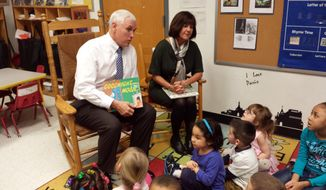 Indiana Gov. Mike Pence and First Lady Karen Pence read to children at the Day Nursery daycare in Indianapolis on Monday, March 3, 2014. Pence is seeking a pilot program that would help pay to send children to preschools and other daycare centers that offer early learning programs.  (AP Photo/Tom LoBianco)