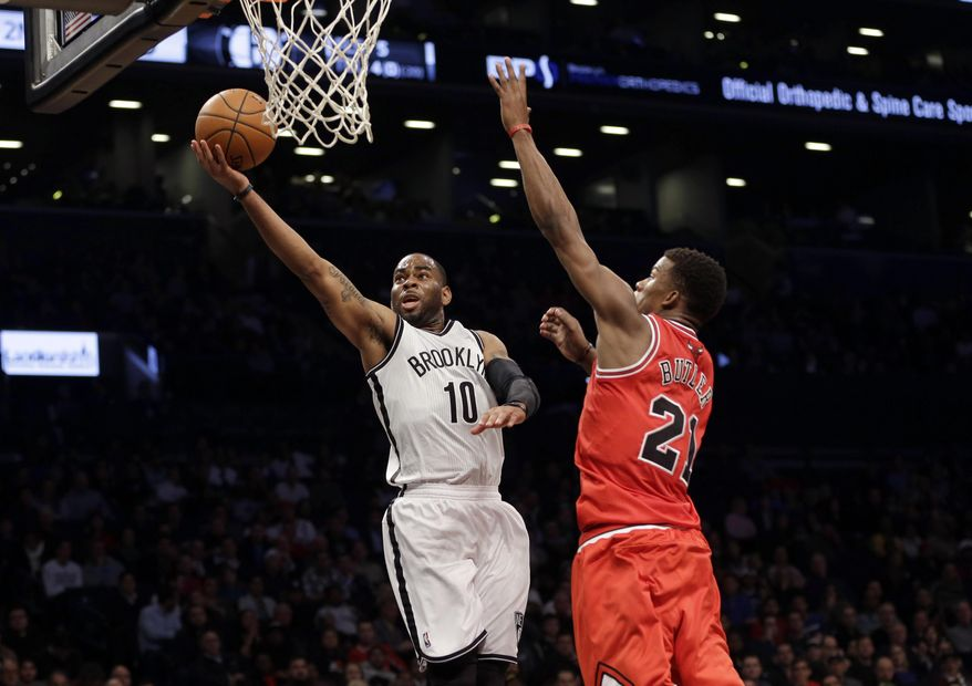 Brooklyn Nets' Marcus Thornton, left, shoots past Chicago Bulls' Jimmy Butler during the first half of an NBA basketball game Monday, March 3, 2014, in New York. (AP Photo/Seth Wenig)