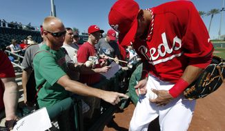 Cincinnati Reds' Billy Hamilton signs an autograph for a fan before an exhibition baseball game against the Seattle Mariners in Goodyear, Ariz., Monday, March 3, 2014. (AP Photo/Paul Sancya)