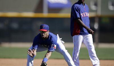 Seattle Seahawks quarterback Russell Wilson, left, fields a ground ball as Texas Rangers second baseman Jurickson Profar, right, stands near during spring training baseball practice, Monday, March 3, 2014, in Surprise, Ariz. (AP Photo/Tony Gutierrez)