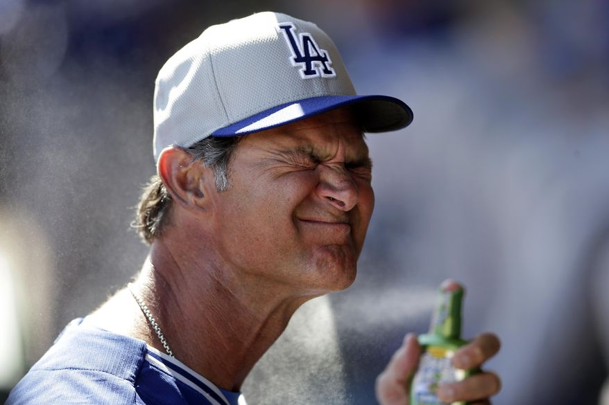Los Angeles Dodgers manager Don Mattingly sprays on suntan lotion in the dugout before the Dodgers play the Oakland Athletics in a spring training baseball game Monday, March 3, 2014, in Phoenix. (AP Photo/Gregory Bull)