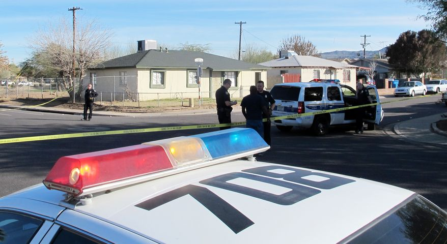 **FILE** Phoenix police gather outside a home in a neighborhood south of downtown Friday, Feb. 1, 2013. (AP Photo/Brian Skoloff)