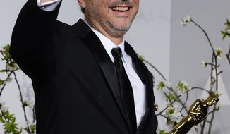 """Alfonso Cuaron poses in the press room with the award for best film editing for """"Gravity"""" during the Oscars at the Dolby Theatre on Sunday, March 2, 2014, in Los Angeles.  (Photo by Jordan Strauss/Invision/AP)"""