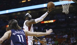 Miami Heat's LeBron James, center,  slides through Charlotte Bobcats players Michael Kidd-Gilchrist (14), Josh McRoberts (11) and Al Jefferson (25) for two points during the first half of an NBA basketball game in Miami, Monday, March 3, 2014. (AP Photo/J Pat Carter)