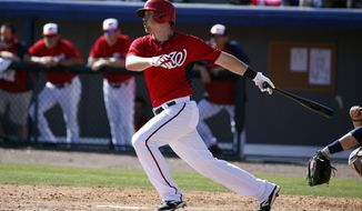 Washington Nationals first baseman Tyler Moore (12) hits a spring exhibition baseball game against the Atlanta Braves, Saturday, March 1, 2014, in Viera, Fla. The Nationals won 16-15. (AP Photo/Alex Brandon)