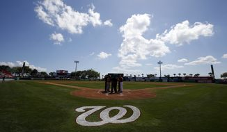 Managers from both teams meet with the umpires at the plate before a spring exhibition baseball game between the Atlanta Braves and the Washington Nationals at Space Coast Stadium, Saturday, March 1, 2014, in Viera, Fla. (AP Photo/Alex Brandon)