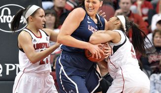 Connecticut's Stefanie Dolson, center, battles Louisville's Tia Gibbs, Left, and Bria Smith for a rebound during the first half of an NCAA college basketball game Monday, March 3, 2014, in Louisville, Ky. (AP Photo/Timothy D. Easley)