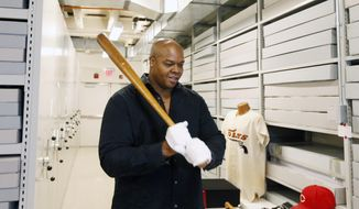 Former Chicago White Sox player Frank Thomas holds a Babe Ruth bat in the archives area during his orientation visit at the Baseball Hall of Fame on Monday, March 3, 2014, in Cooperstown, N.Y. Thomas will be inducted to the hall in July. (AP Photo/Mike Groll)