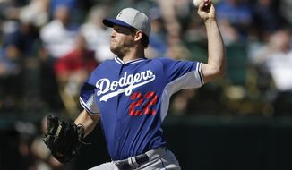 Los Angeles Dodgers pitcher Clayton Kershaw pitches to an Oakland Athletics batter during the first inning of a spring training baseball game Monday, March 3, 2014, in Phoenix. (AP Photo/Gregory Bull)