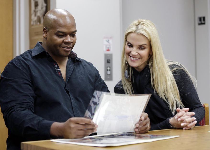 Former Chicago White Sox player Frank Thomas and wife Megan look at old photos of his playing days during an orientation visit at the Baseball Hall of Fame on Monday, March 3, 2014, in Cooperstown, N.Y. Thomas will be inducted to the hall in July. (AP Photo/Mike Groll)