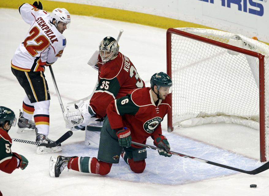 Minnesota Wild goalie Darcy Kuemper, center, looks to teammate Marco Scandella, right, to clear away the puck as Calgary Flames' Lee Stempniak, left, stands near in the first period of an NHL hockey game, Monday, March 3, 2014, in St. Paul, Minn. (AP Photo/Jim Mone)