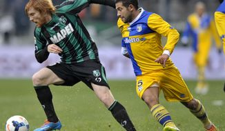 Sassuolo's Davide Biondini, left, vies for the ball with Parma's Walter Gargano of Uruguay, during their Serie A soccer match at Reggio Emilia's Mapei stadium, Italy, Sunday, March 2, 2014. (AP Photo/Marco Vasini)