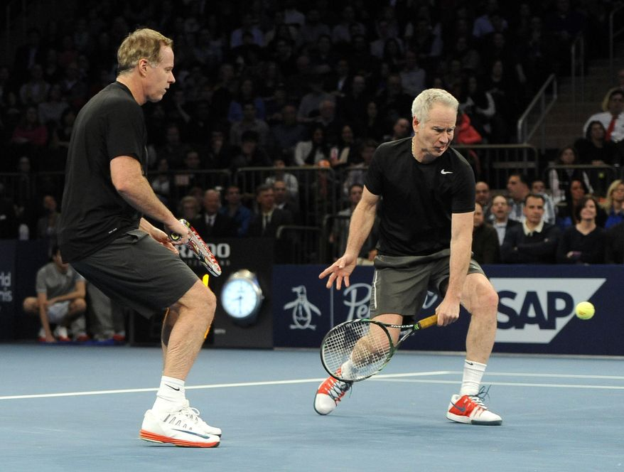 Patrick McEnroe, left, watches his brother John return a shot against Mike and Bob Bryan in the BNP Paribas Showdown Tennis Tournament on Monday, March 3, 2014, in New York. The Bryans won 8-3. (AP Photo/Kathy Kmonicek)