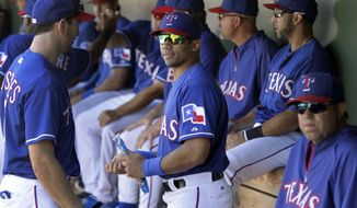 Seattle Seahawks quarterback Russell Wilson, center, talks with Texas Rangers' Adam Rosales, left, as he stands in the dugout during a spring training exhibition baseball game against the Cleveland Indians, Monday, March 3, 2014, in Surprise , Ariz. (AP Photo/Tony Gutierrez)