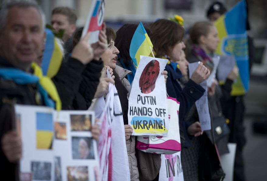 Ukrainians living in Italy protest outside the Russian embassy, in Rome, Monday, March 3, 2014. Demonstrators condemned Russian military actions in Ukraine. (AP Photo/Andrew Medichini)