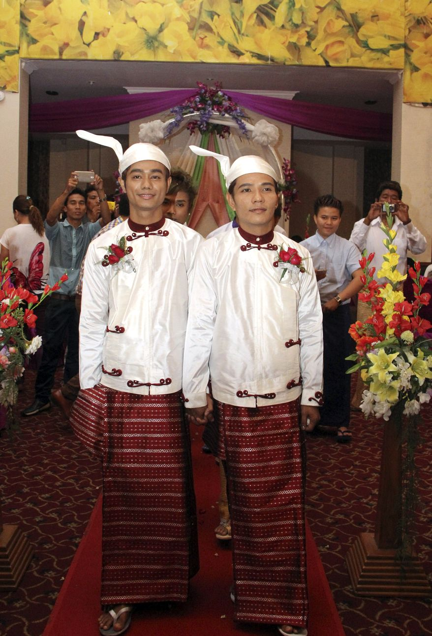 In this March 2, 2014 photo, Myo Min Htet, left, walks along with Tin Ko Ko, during their wedding reception at Excel Tower in Yangon, Myanmar.  Ten years after they fell in love and moved in together, Tin Ko Ko, 38, and Myo Min Htet, 28, over the weekend became Myanmar's first gay couple to publicly get married. (AP Photo/Khin Maung Win)