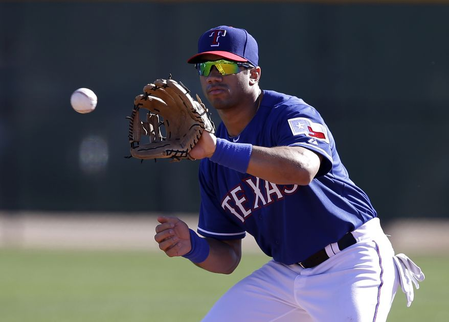 Seattle Seahawks quarterback Russell Wilson reaches up to grab a throw as he works out with the Texas Rangers during spring training baseball practice, Monday, March 3, 2014, in Surprise, Ariz. (AP Photo/Tony Gutierrez)