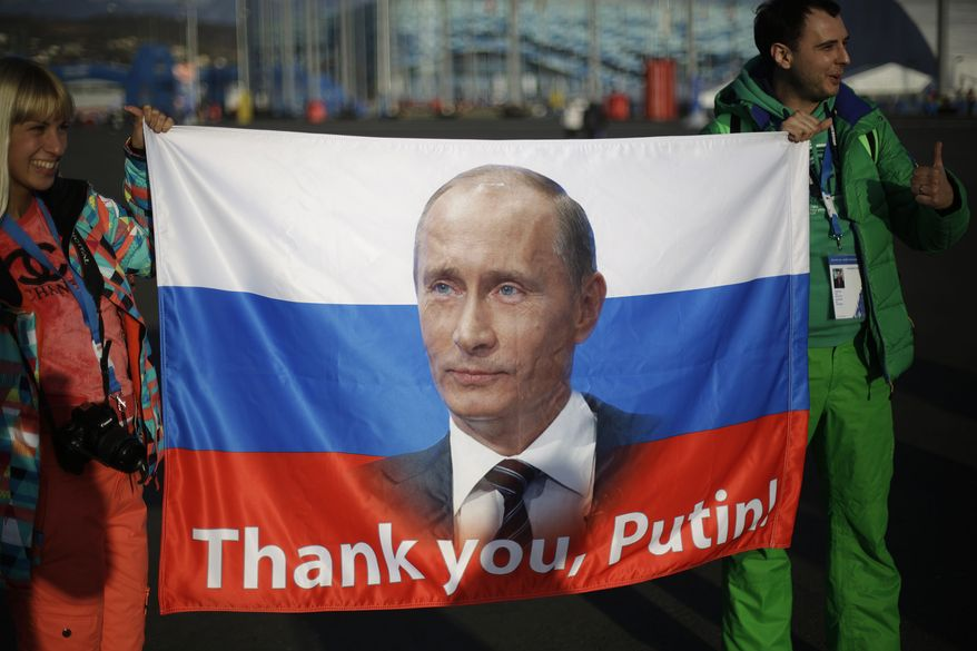 """Veleriya Obarevich, left, and Yan Shamilov carry a Russian flag with the message """"Thank you, Putin!"""" written across it through the Olympic Park ahead of the 2014 Winter Olympics closing ceremony, Sunday, Feb. 23, 2014, in Sochi, Russia. (AP Photo/David Goldman)"""