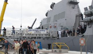 Passengers from a disabled Canadian naval ship walk off the American naval destroyer USS Michael Murphy after being escorted to Pearl Harbor, Hawaii, Tuesday, March 4, 2014. A U.S. Navy ocean tug was towing the Canadian ship after an engine fire left 20 sailors with minor injuries. (AP Photo/Oskar Garcia)