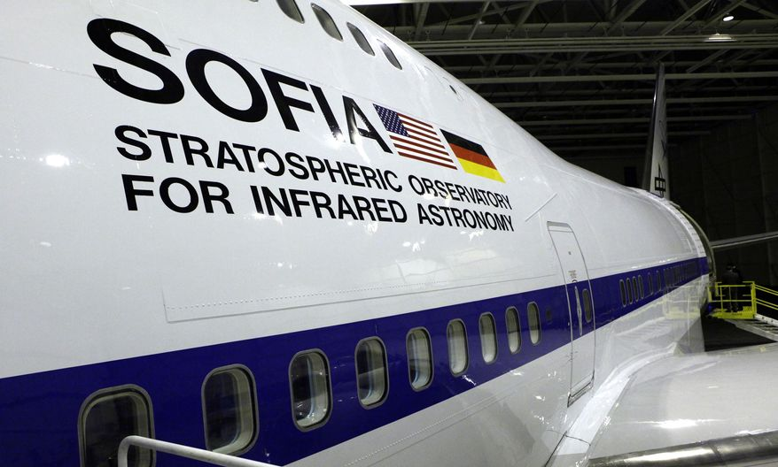 FILE - In this April 20, 2010, file photo, U.S. and German flags are seen on the side of the aircraft at the first public viewing of the Stratospheric Observatory for Infrared Astronomy (SOFIA), a cooperative venture between NASA and German scientists, where a 2.8-meter (98-inch) telescope has been mounted inside specially modified Boeing 747-SP, at the NASA Dryden Flight Research Center test facility in Palmdale, Calif. The White House released its budget on Tuesday, March 4, 2014, that proposes to mothball the observatory unless Germany and other partners can kick in more money. (AP Photo/Reed Saxon, File)