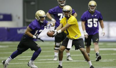 Washington redshirt quarterback Troy Williams hands the ball off to tailback Dwayne Washington, left, on the first day of spring NCAA college football practice, Tuesday, March 4, 2014 in Seattle. (AP Photo/Ted S. Warren)