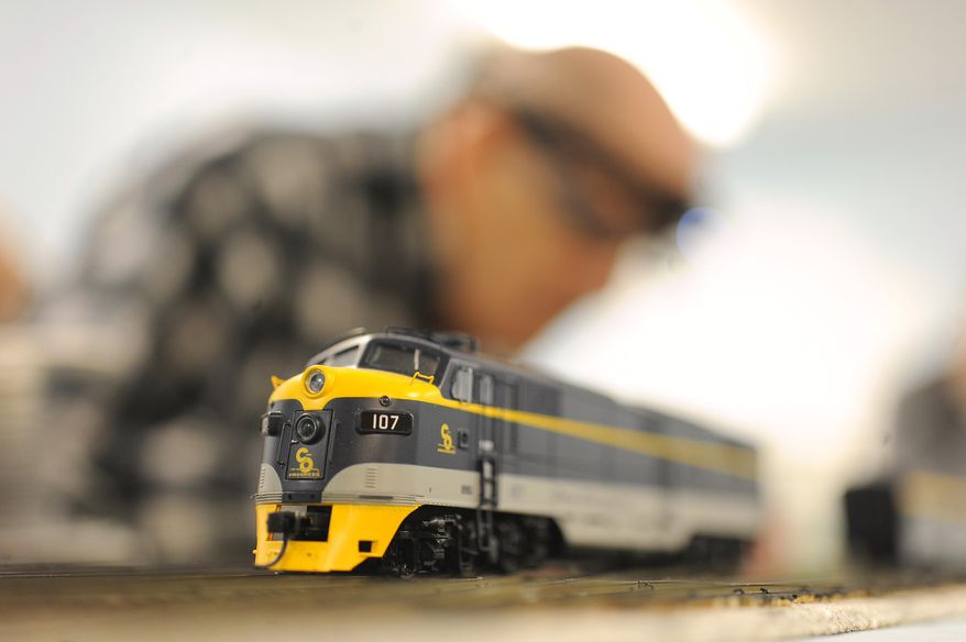 In this photo taken on Thursday Feb. 27, 2014, Jack Kerby, 83,member of the Fox Run Model RailRoad Club inserts metal spikes on the railroad track as a Chesapeake & Ohio engine rests in the foreground a at the Fox Run Retirement community in Novi, Mich. (AP Photo/Detroit News,  Max Ortiz)  DETROIT FREE PRESS OUT; HUFFINGTON POST OUT