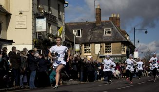First place finisher Devon Byrne, left, from Olney, leads the field en route to winning the annual Shrove Tuesday trans-Atlantic pancake race for the third time in a record time of 55.61 seconds, in the town of Olney, in Buckinghamshire, England, Tuesday, March 4, 2014.  Every year women clad in aprons and head scarves from Olney and the city of Liberal, in Kansas, USA, run their respective legs of the race with a pancake in their pan, flipping it at the beginning and end of the race.  According to legend, the Olney race started in 1445 when a harried housewife arrived at church on Shrove Tuesday still clutching her frying pan with a pancake in it.  Liberal challenged Olney to a friendly international competition in 1950 after seeing photos of the race in a magazine.  (AP Photo/Matt Dunham)