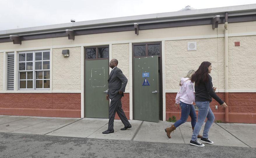 Charles Ramsey, president of the West Contra Costa school board, walks out of a boys bathroom where police were investigating reports of a brutal assault of a transgender teen at the Hercules Middle-High School campus in Hercules, Calif., Tuesday, March 4, 2014. The 15-year-old student told officers he was leaving a boy's bathroom at Hercules High School on Monday when three teenage boys pushed him inside a handicapped stall and physically and sexually assaulted him, Hercules police Detective Connie Van Putten said. (AP Photo/Jeff Chiu)