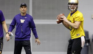 New Washington head football coach Chris Petersen, left, stands near redshirt quarterback Jeff Lindquist, right, as Lindquist passes on the first day of spring NCAA college football practice, Tuesday, March 4, 2014, in Seattle. (AP Photo/Ted S. Warren)