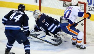 New York Islanders' Michael Grabner (40) scores on Winnipeg Jets goaltender Ondrej Pavelec (31) as Zach Bogosian (40) watches during overtime of an NHL hockey game in Winnipeg, Manitoba, Tuesday, March 4, 2014. The Islanders won 3-2. (AP Photo/The Canadian Press, Trevor Hagan)