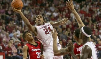 Arkansas guard Michael Qualls (24) leaps around Georgia guard J.J. Frazier (30) during the second half of an NCAA college basketball game on Saturday, March 1, 2014, in Fayetteville, Ark. Arkansas defeated 87-75. (AP Photo/Gareth Patterson)