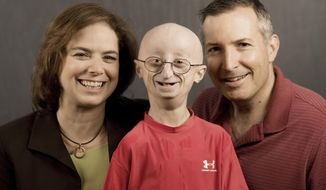 """FILE - This undated photo provided by HBO shows Sam Berns, the subject of the HBO documentary, """"Life According to Sam,"""" center, with his parents, Leslie Gordon, left, and Scott Berns. The Foxborough School Committee on Monday, March 3, 2014 approved naming a new athletic field at Foxborough High School in honor of Berns, the former student who died of a rare genetic condition that accelerates the aging process. (AP Photo/HBO, Sean Fine, File)"""