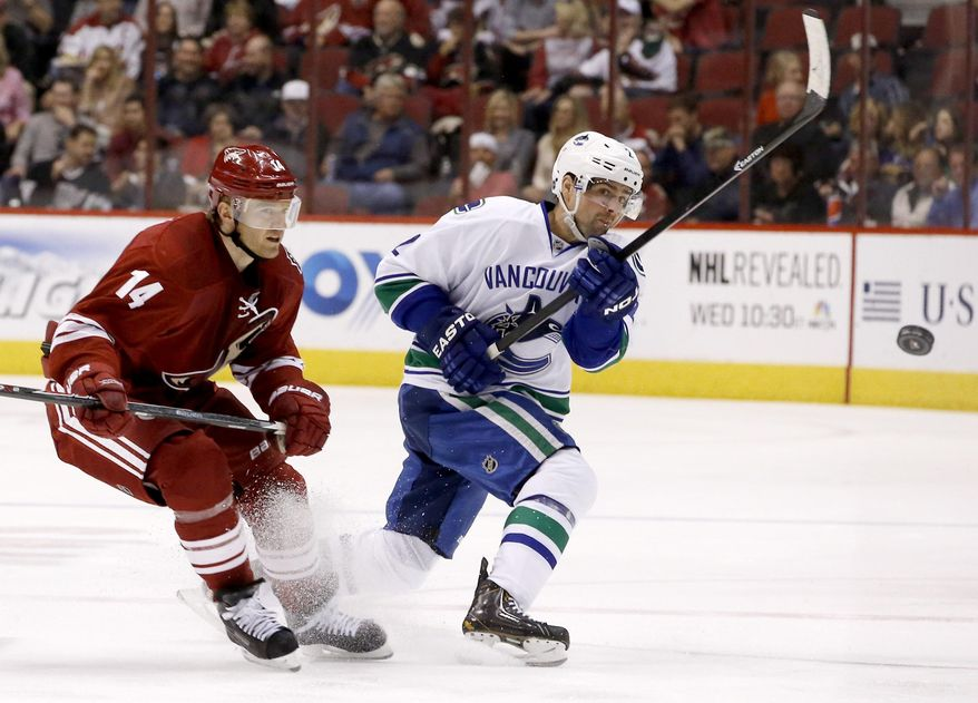 Vancouver Canucks' Dan Hamhuis, right, sends the puck into the air as Phoenix Coyotes' Jeff Halpern (14) arrives to apply pressure during the first period of an NHL hockey game on Tuesday, March 4, 2014, in Glendale, Ariz. (AP Photo/Ross D. Franklin)