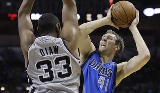Dallas Mavericks' Dirk Nowitzki (41), of Germany, shoots over San Antonio Spurs' Boris Diaw (33), of France, during the second half of an NBA basketball game, Sunday, March 2, 2014, in San Antonio. San Antonio won 112-106. (AP Photo/Eric Gay)