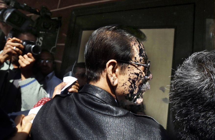 Chairman of Sahara India Pariwar Subrata Roy, his face smeared with ink thrown by a lawyer, walks into the Supreme Court in New Delhi, India, Tuesday, March 4, 2014. A lawyer threw ink at the top Indian businessman as he arrived at India's highest court Tuesday to face charges that his company failed to return billions of dollars to investors. Roy's Sahara conglomerate is well known throughout India because it co-owns a Formula One team and sponsored the Indian cricket team until recently. (AP Photo/Altaf Qadri)