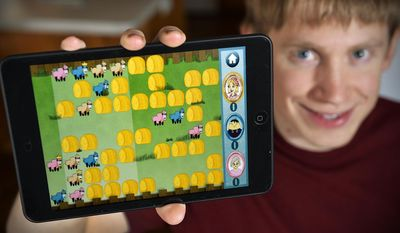 """ADVANCE FOR USE SATURDAY, MARCH 8 - In this photo taken on Feb. 8, 2014, Sartell High School and University of Minnesota computer science graduate David Hanson poses for a photo in in Sartell, Minn., as he shows the iOS version of his game, """"Shuffling Sheep"""" that was released Jan. 9, 2014. The game was inspired by classic children's strategy-based board games, specifically one called """"Shuttles,"""" released in 1973. But it's challenging enough to keep adults interested. (AP Photo/The St. Cloud Times, Kimm Anderson)  NO SALES"""