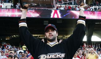 Anaheim Ducks' Dustin Penner hoists the Stanley Cup as he walks out of Los Angeles Angels dugout prior to the start of the baseball game between Houston Astros and the Angels in Anaheim, Calif., Tuesday, June 19, 2007. (AP Photo/Kevork Djansezian)