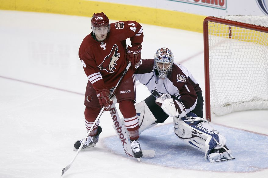 Phoenix Coyotes' Chris Brown, left, screens Colorado Avalanche's Semyon Varlamov, right, of Russia, during an NHL hockey game Saturday, April 6, 2013, in Glendale, Ariz. (AP Photo/Paul Connors)