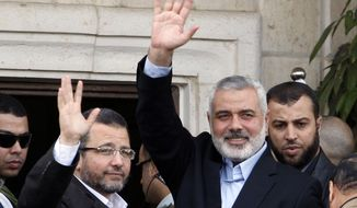 FILE - In this Friday, Nov. 16, 2012 file photo, Gaza's Hamas Prime Minister Ismail Haniyeh, right, and Egyptian Prime Minister Hesham Kandil, left, waves to the crowd as they meet in Gaza City. An Egyptian court ruled on Tuesday, March 4, 2014 to ban activities of the Palestinian militant group Hamas in Egypt in a move likely to fuel tension between Cairo's military-backed government and the Islamic group that rules the neighboring Gaza Strip. Egypt's interim leaders maintain that Hamas is playing a key role in the insurgency by militants in the northern region of the Sinai Peninsula, which borders Hamas-ruled Gaza and Israel. (AP Photo/Adel Hana, File)