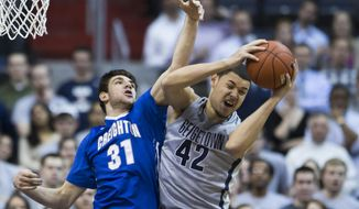 Georgetown center Bradley Hayes (42) pulls down a rebound over Creighton center Will Artino (31) during the first half of an NCAA basketball game on Tuesday, March 4, 2014, in Washington. (AP Photo/ Evan Vucci)