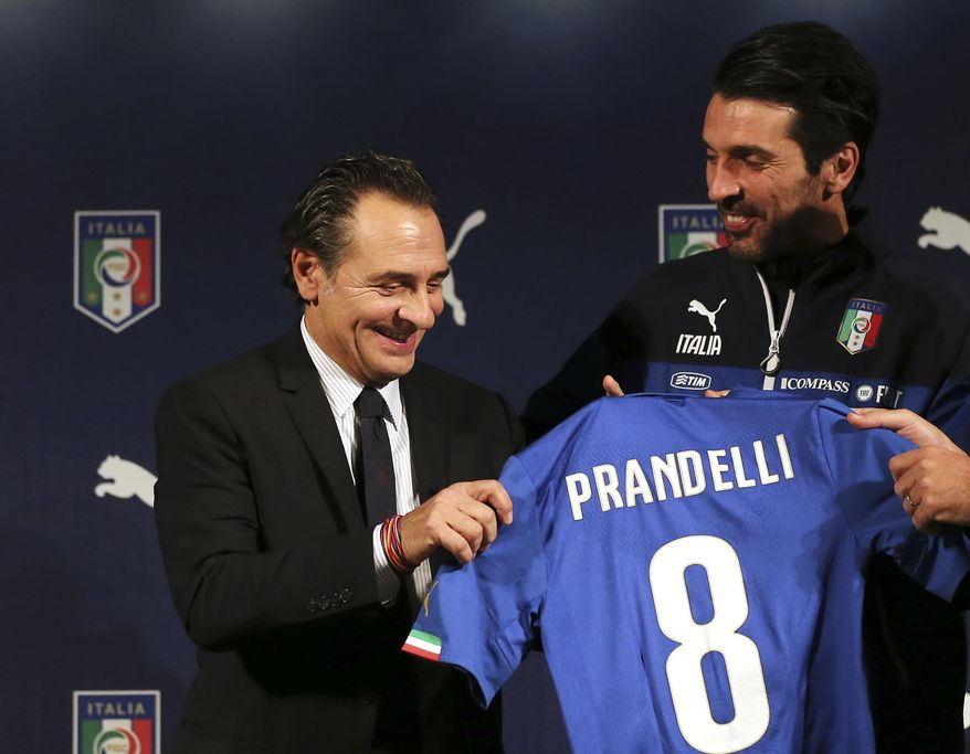 Italy coach Cesare Prandelli , left, and goalkeeper Gianluigi Buffon show a new Italy soccer team jersey bearing the name of Prandelli  during a press conference in Milan, Italy, Monday, March 3, 2014.  Mario Balotelli is out injured and Daniele De Rossi has been dropped due to a code of ethics violation for Italy's friendly at World Cup holder Spain on Wednesday. Missing two key starters, coach Cesare Prandelli gave Torino forward Ciro Immobile and Parma defender Gabriel Paletta their first call ups to Italy's squad on Sunday. (AP Photo/Antonio Calanni)