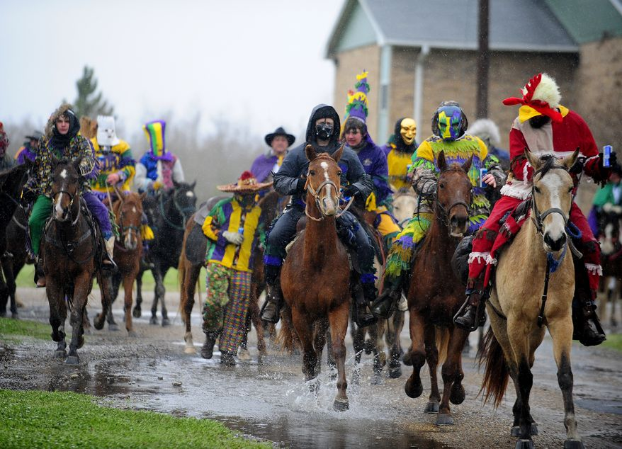 Costumed runners ride in the Courir de Mardi Gras à Grand Mamou in Mamou, La., Tuesday, March 4, 2014. Participants continue the tradition of chasing chickens and traveling to local homes to gather ingredients for a community gumbo. (AP Photo/The Daily Advertiser, Paul Kieu) NO SALES