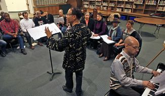 In this Feb. 27, 2014 photo, Daryl Walker, center, the director of The Spirituals Project Choir, oversees a rehearsal of his group, inside a church, in Denver. As The Spirituals Project enters its third decade, founder Arthur Jones is trying to spread the power he believes the music holds to build community across lines of race and class, and to move individuals to address personal and political challenges. (AP Photo/Brennan Linsley)